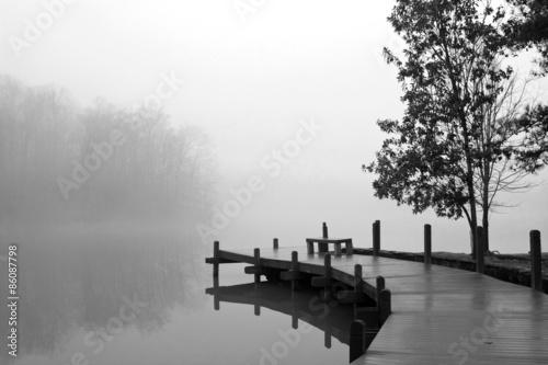 Fototapeta Thick Blanket Of Fog Covers Lake And Wooden Dock