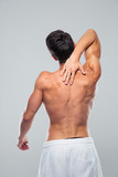 Rear view portrait of a muscular man with neck pain