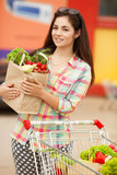 Happy woman in market girl with vegetables at grocery