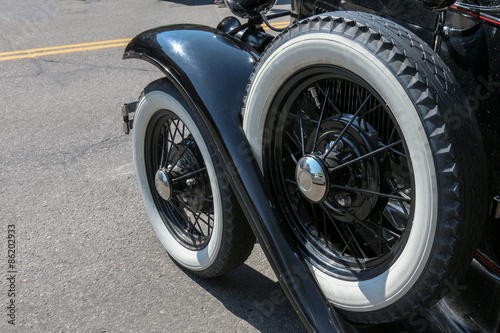 Poster Whitewall tire and handy spare on a 1930's vintage black sedan style car, close