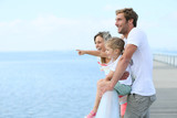 Fototapety Family standing on a pontoon looking at the sea