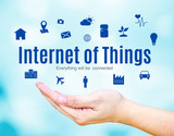 Open hand with Internet of Things (IoT) word and icon on blue bl poster