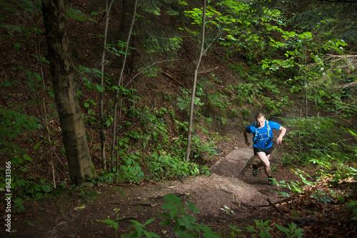 mata magnetyczna Pojedynczy człowiek działa pod górę na szlak w lesie