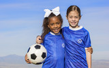 Cute, young african american and hispanic female soccer players holding a ball with a simple blue sky background