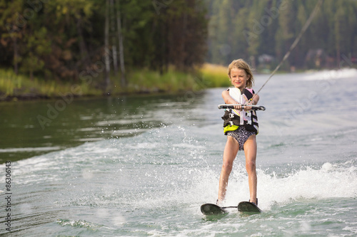 Papiers peints Nautique motorise Young Waterskier water skiing on a beautiful scenic lake. Lots of copy space with scenic background