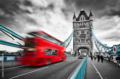 Red bus in motion on Tower Bridge in London, the UK Poster