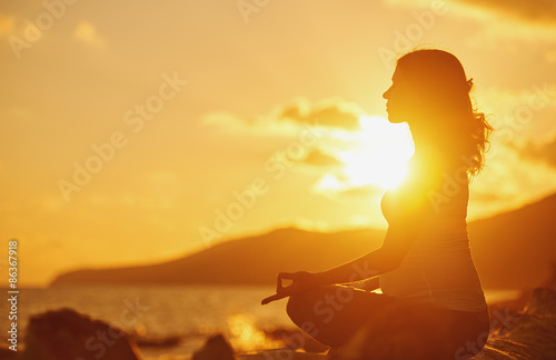 Poster Pregnant woman practicing yoga in lotus position on beach at sun