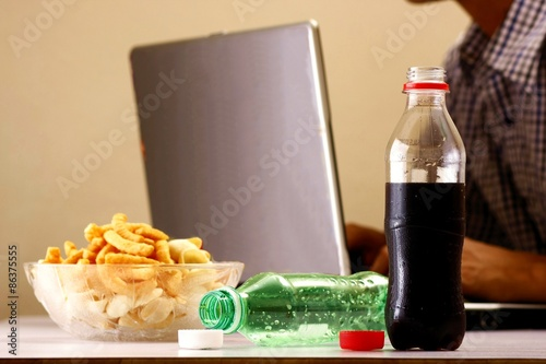 Poster Bottles of softdrinks or soda, chips and man working on a laptop computer in the