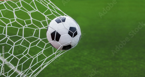 Fototapeta soccer ball in goal with green backgroung