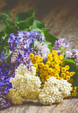 Bouquet of herbs and wild flowers on old wooden table in vintage