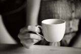 Cup of tea in woman hand, b&w with film grain