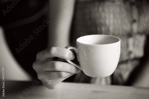 Cup of tea in woman hand, b&w with film grain  - 86507983