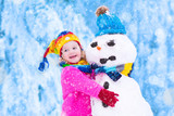 Fototapety Little girl playing with a snowman
