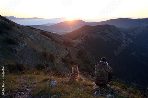 Poster uomo e cane guardano il tramonto