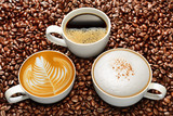 Variety of cups of coffee on coffee beans background