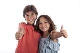 Niño y niña sonriendo y levantando el pulgar