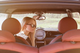 Nice portrait of blonde young woman at the wheel of sport car with red interior, with sunglasses