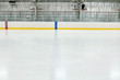 View across the empty ice of an indoor hockey rink with metal bleachers