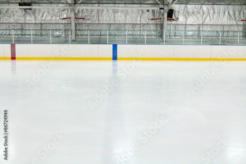 View across the empty ice of an indoor hockey rink with metal bleachers Poster