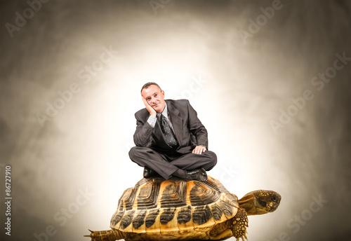 Poster uomo d'affari seduto sopra una tartaruga gigante