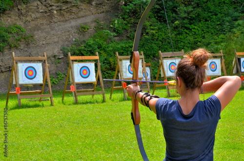 Poster Junge Frau beim Bogenschiessen