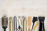 Hairdressing tools on wooden background with copy space at top