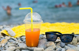Fototapeta Juice with drinking straw and sunglasses on beach near sea
