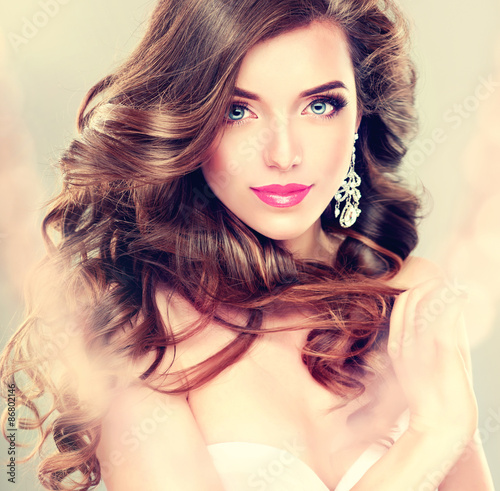 Leinwand Poster Beautiful model brunette with long curled hair and jewelry earrings