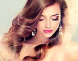 Fototapety Beautiful model brunette with long curled hair and jewelry earrings