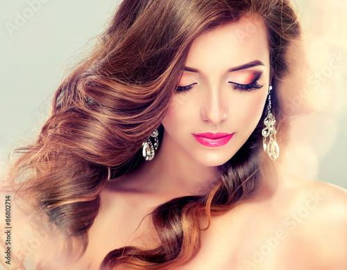 Poster Schöne Modell Brunette mit dem langen gekräuselten Haar und Schmuck Ohrringe