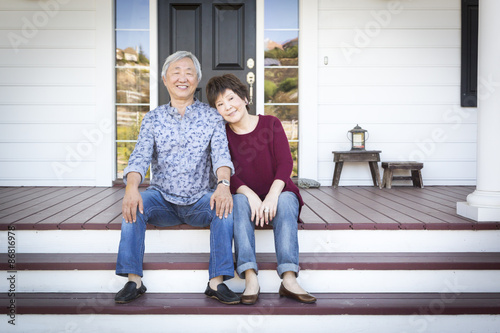 Poster Senior Chinese Couple Sitting on Front Steps of Their House