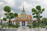 Grounds of Wat Arun in Bankgkok Thailand feature distinctive temple architecture with guardian figures and and decorative gardening poster