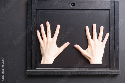 Two hands on black window hatch Poster