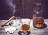 Fototapeta Cognac and cigar burning on a wooden table