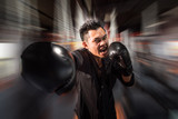 young aggressive businessman training shadow boxing at gym with gloves throwing vicious punch in angry rage face expression, fighting business concept, motion blur background. poster