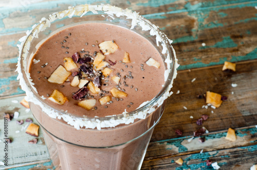 Foto op Aluminium Milkshake Chocolate coconut smoothie milkshake blended with cacau, coconut milk, banana and topped with coconut flakes and chia seeds. A healthy snack or treat served in a tall glass on a rustic wooden table.