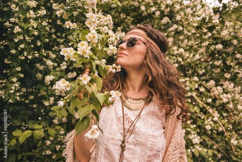 Valokuva bohemian young woman enjoying flowers fragrance