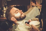 Fototapety Client during beard shaving in barber shop