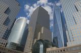 Downtown Manhattan skyline featuring modern shiny skyscrapers under bright blue sky - 87237185