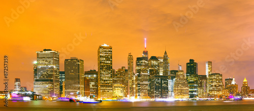Poster New York City skyline, financial district colorful illuminated buildings in downtown Manhattan at sunset