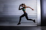 Muscular woman running in exercise room - 87260947
