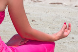 Young woman is doing exercises yoga on the seashore,Photography