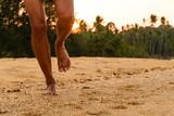 Fototapety Barefoot running on beach at sunset.