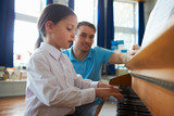 Fototapety Female Student Enjoying Piano Lesson With Teacher
