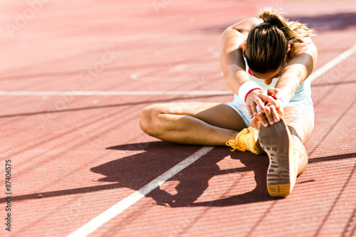Beautiful young athletic woman stretching in summer Plakát
