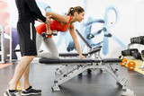 Fototapety Young male trainer giving instructions to a woman in a gym