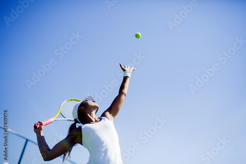 Beautiful female tennis player serving Poster