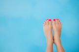 Gołe stopy nad błękitną wodą w basenie