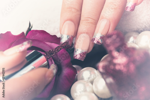 Manicure - Beauty treatment photo of nice manicured woman fingernails. Very nice feminine nail art with silver and purple glitter nail polish. Processed in retro, vintage colors. © tamara83