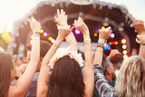 Fototapety Audience with hands in the air at a music festival